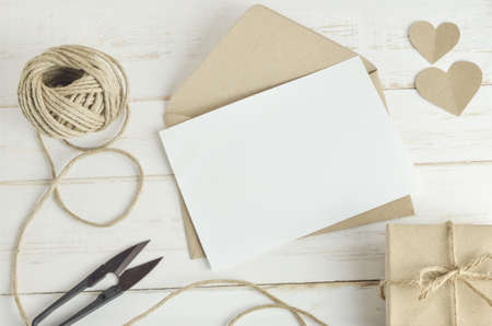 Leere weiße Grußkarte mit braunen Umschlag und handgemachte Geschenk-Box auf alten Holztisch mit Vintage-Ton