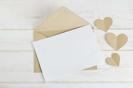 Blank white greeting card with brown envelop and heart tag on old wooden table with soft vintage  tone