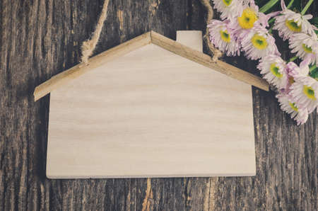 Blank wooden sign with house shape and Mum flower on old wooden table with vintage and vignette tone