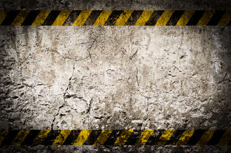 Hazard tape on blank dirty wall background with grunge and vignette tone