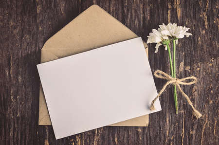 wither: Blank white greeting card with brown envelope and wither Mum flowers on wooden table with vintage and vignette tone Stock Photo