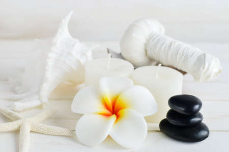 massage herbal: Plumeria flower spa soap with seashells, black stone, massage herbal ball and white aromatherapy candles on white vintage wooden table