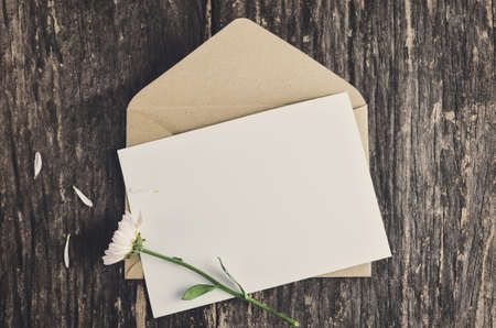 Blank white greeting card with brown envelope and wither Mum flowers on wooden table with vintage and vignette tone 写真素材
