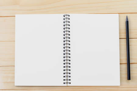 Open Notebook and black pencil on wooden background