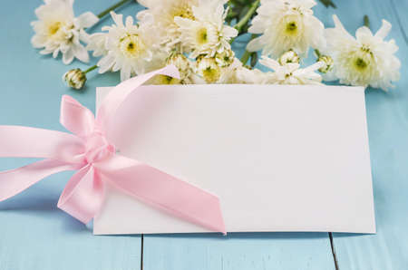 Blank white greeting card with pink ribbon bow and white Chrysanthemum flowers on blue wooden background