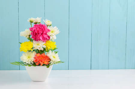 Bunch of colorful flowers in white vase, pink Carnation and Chrysanthemum flowers on blue and white wooden background