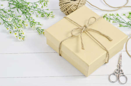Brown gift box with recycle ribbon bow on wooden background with white daisy flower and vintage tone