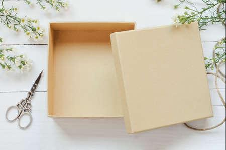 caja de regalo de color marrón abierta en el fondo de madera con la flor de la margarita blanca y el tono de la vendimia Foto de archivo