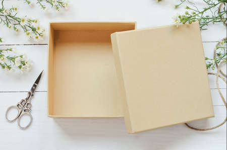 Opened brown gift box on wooden background with white daisy flower and vintage tone Stockfoto