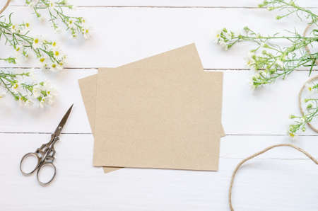 Blank greeting card with brown envelop and daisy flowers on white wooden table with vintage tone