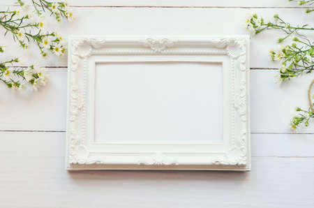 Blank vintage photo frame on white wooden background with daisy flowers and soft vintage tone