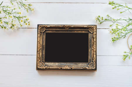 pinchbeck: Blank vintage photo frame on white wooden background with daisy flowers and soft vintage tone