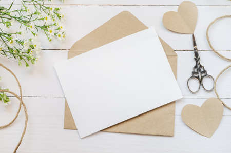 Blank white greeting card with brown envelop and daisy flowers on wooden table with vintage tone
