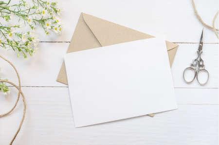 빈티지 흰색과 나무 테이블에 갈색 봉투와 데이지 꽃과 빈 흰색 인사말 카드