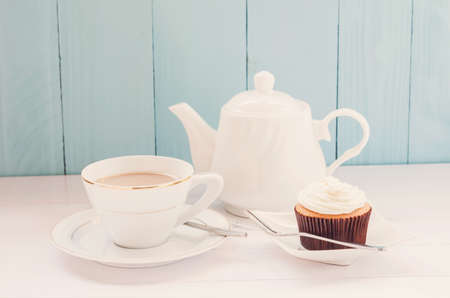 vanilla cupcake: Tea time, Vanilla cupcake with cup of milk tea and white teapot on blue and white wooden background with soft vintage tone
