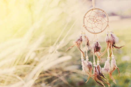 Close up of Dream Catcher on meadow background with soft vintage tone Foto de archivo