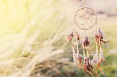 Zbliżenie na łapacz snów na tle łąki z miękkim tonem vintage
