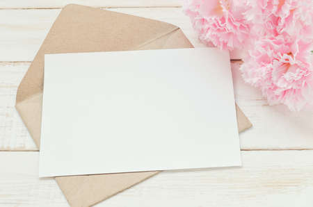 Blank white greeting card with brown envelope and pink carnation flower on wooden table with vintage and vignette tone