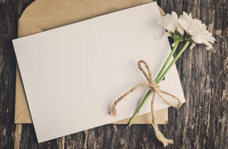Close up of blank white greeting card with brown envelope and wither Mum flowers on wooden table with vintage and vignette tone 写真素材