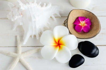 aromatherapy candle: Plumeria flower spa soap with seashells, black stone and pink aromatherapy candle on white vintage wooden table Stock Photo
