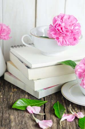 Pink pastel carnation flowers in white tea cup and vase on pile pink pastel carnation flowers in white tea cup and vase on pile of books on wooden mightylinksfo