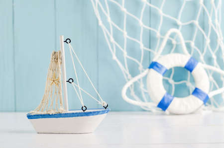 animal figurines: Antique sail boat Toy model with rope and seashell on white and blue wooden background - Nautical background