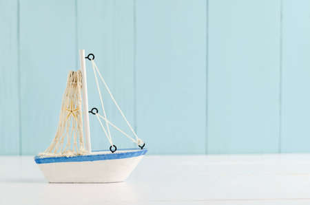 trawl: Antique sail boat Toy model with rope and seashell on white and blue wooden background - Nautical background