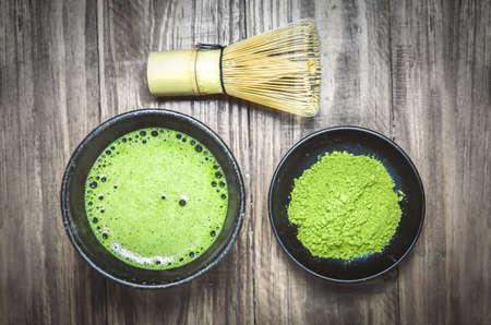 Japanische Matcha Grüntee und Matcha Grüntee-Pulver bei hausgemachten Tonschale mit Bambusbesen auf Holztisch mit Vignette-Ton