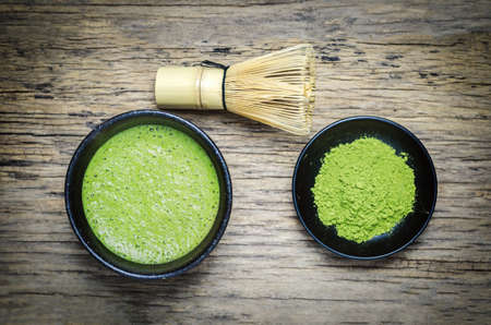 Japanese matcha green tea and matcha green tea powder at homemade clay bowl with bamboo whisk on wooden table with vignette tone Stock fotó