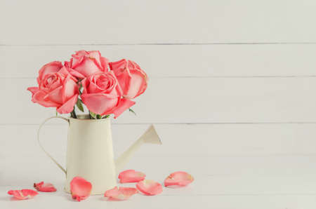 sear: Withered pink rose flowers at watering can on white wooden background with vintage tone Stock Photo