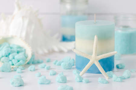 aroma therapy: Blue and white layered candle with starfish seashell and aroma therapy spa salt on white wooden background, Romantic candle background, Spa candle