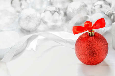 glitter ball: Christmas Background - Red glitter christmas ball with red ribbon bow on white background with silver glitter ball and bokeh light