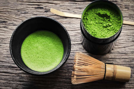 Japanese matcha green tea and matcha green tea powder at homemade clay bowl with bamboo whisk on wooden table with vignette tone Standard-Bild