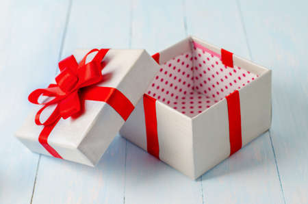 Close up of silver gift box with red polka dot pattern and red ribbon opened on blue wooden background