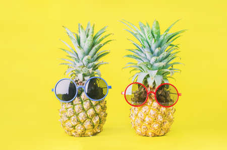 Pineapples with red and blue sunglasses on yellow background - Summer background Stock Photo