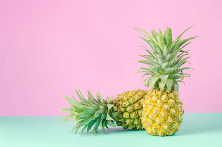Pineapples on blue and pink pastel background - Summer background Stock Photo