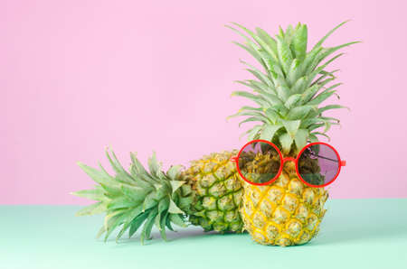 Pineapples with red sunglasses on yellow background - Summer background
