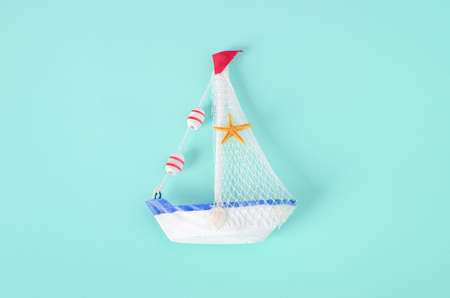 Antique sail boat Toy model with rope and seashell on white and blue background - Nautical background