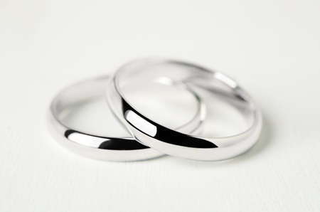Close up of couple wedding rings on white wooden background