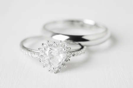 Close up of couple wedding diamond rings on white wooden background