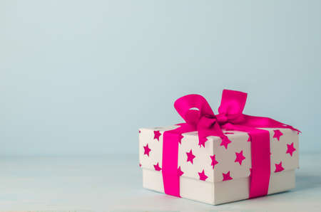 White gift box with pink star pattern and pink ribbon bow on blue wooden background - Christmas background