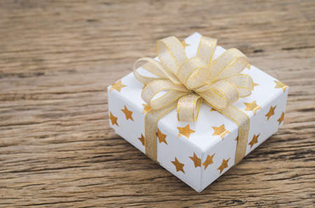 Close up of white gif box with golden star pattern and gold ribbon bow on wooden background - Christmas background