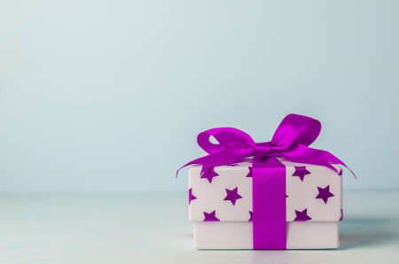 White gift box with purple star pattern and purple ribbon bow on blue wooden background - Christmas background