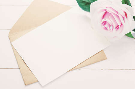 Blank white greeting card with brown envelope and purple rose flower on white wooden background