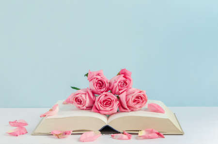 Pink pastel rose flowers with open book on white and blue wooden background with vintage tone