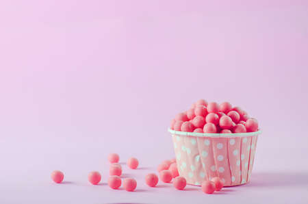 Pink candies in pink paper cup with white polka dot pattern on pink background 写真素材