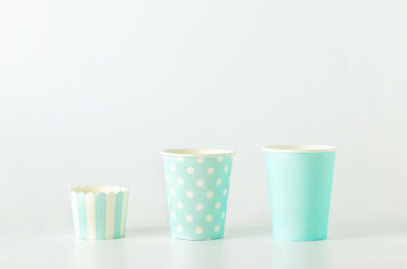 Different size of blue paper cup with white polka dot and striped pattern on white background