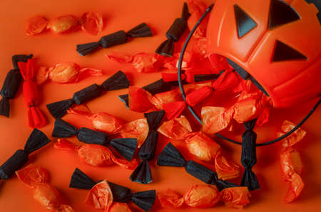 Halloween background - Close up of black and orange candies with pumpkin bag on orange background 写真素材