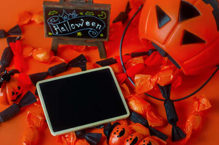 Halloween background - Blank black wooden tag with pumpkin bag, black and orange candies on orange background 写真素材