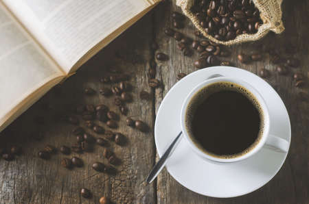 White cup of black coffee on wooden table with coffee beans and open book with vintage and viggnete tone 写真素材